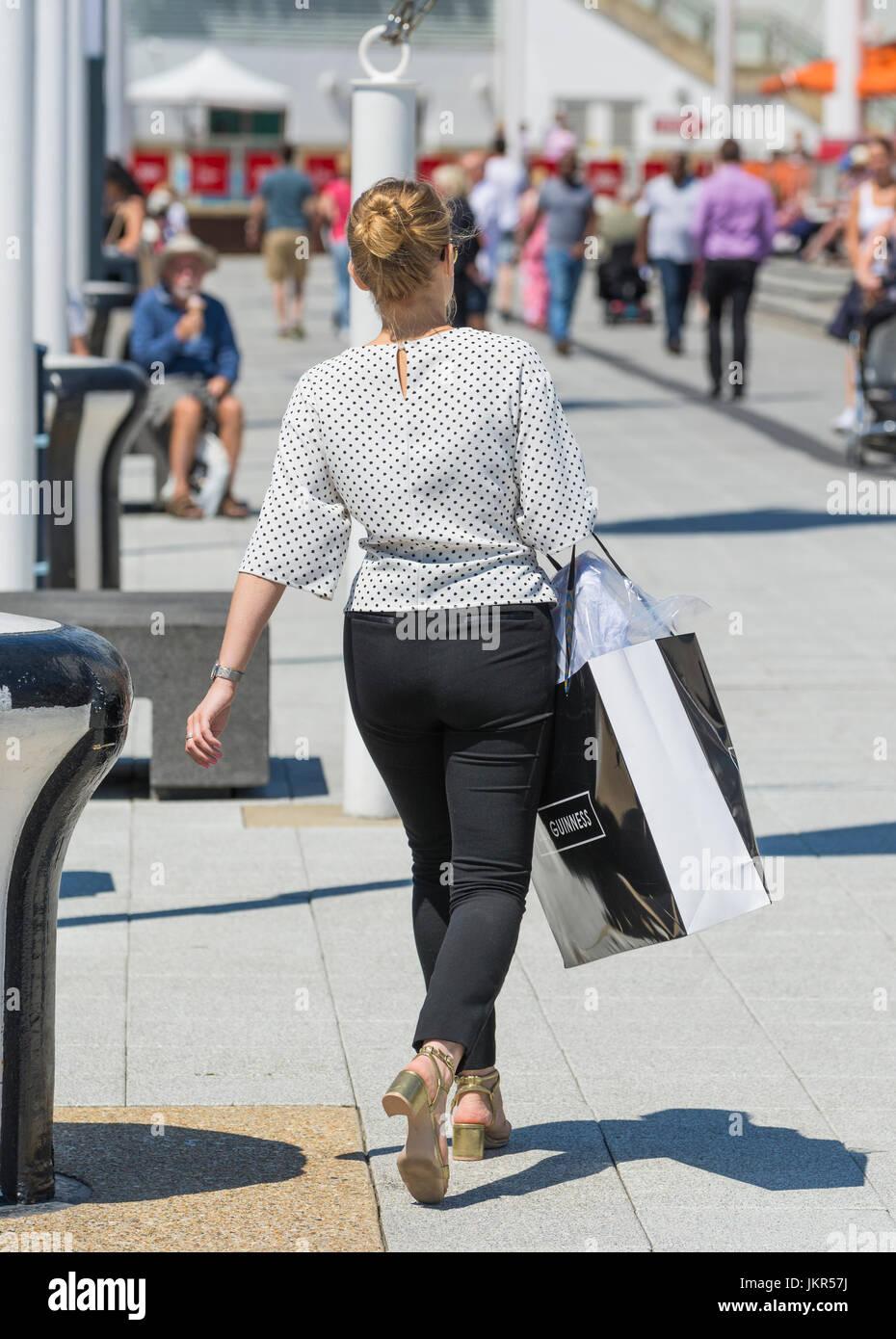 Junge Edel Frau Wandern, gekleidet mit Vorliebe für teure Dinge, tragen Kleidung Shopping Tasche. Stockbild