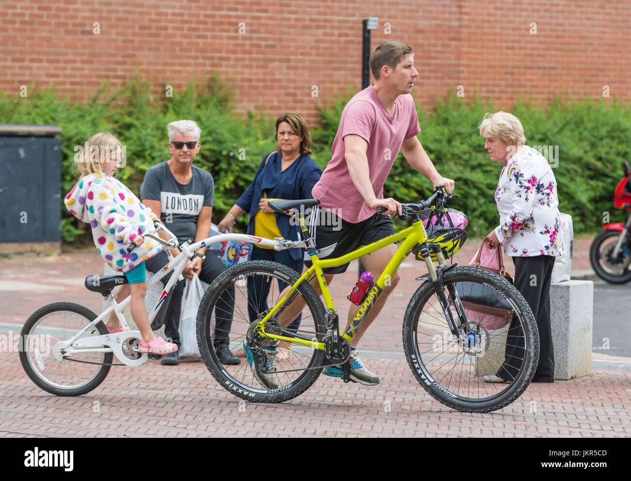 Fahrradanhänger für ein Kind hinter ein Erwachsener Radfahrer fahren mitkommen. Stockbild
