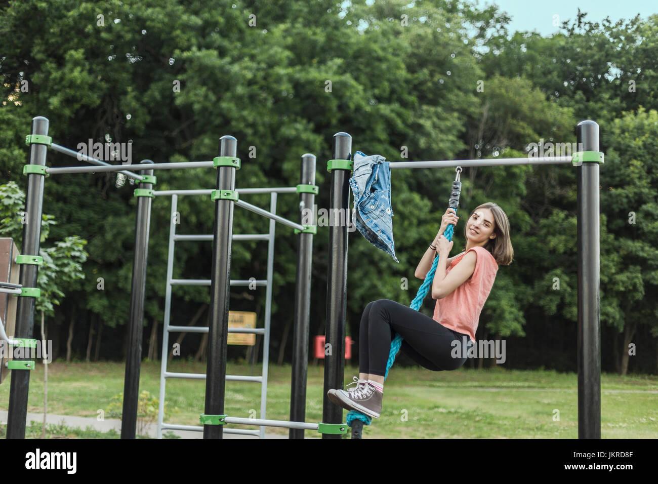 Klettergerüst Mit Seilen : In voller länge portrait von lächelnde junge frau hängen vom