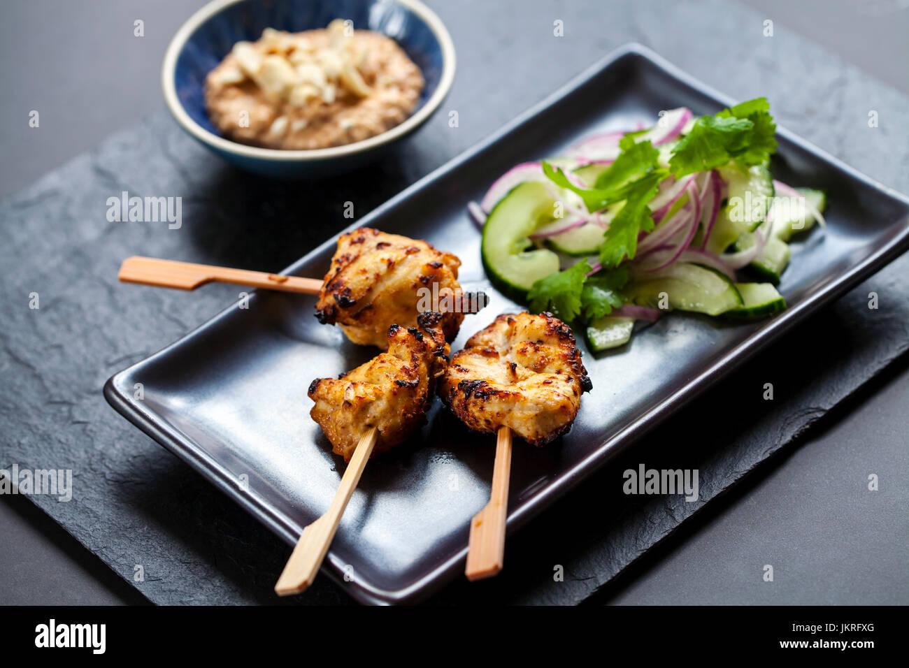 Chicken Satay, Zwiebel und Gurke Salat Stockbild