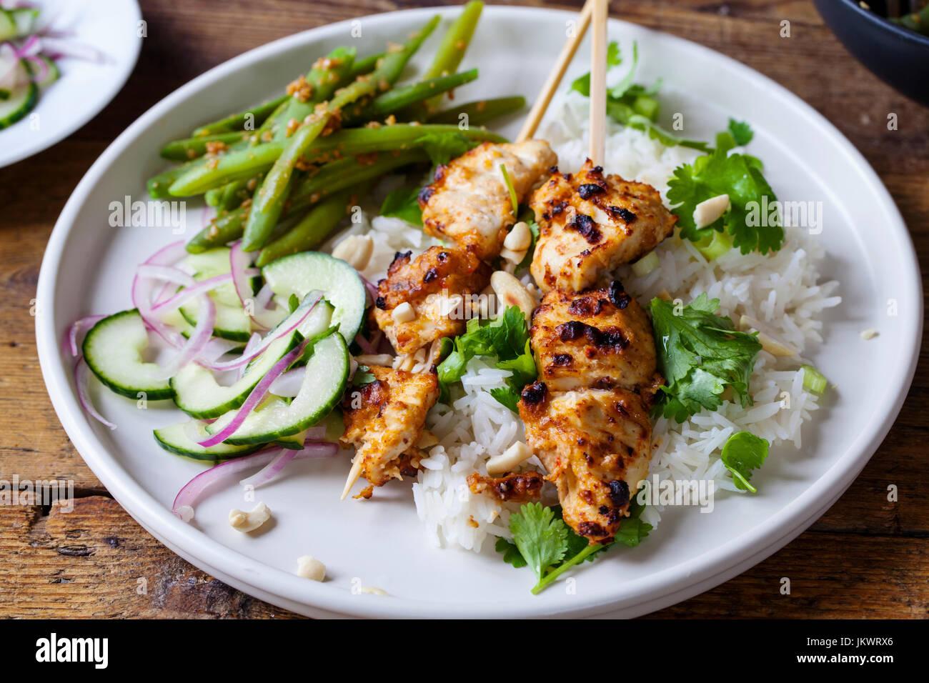 Satay-Hähnchen-Spieße mit grünen Bohnen, Reis und Gurkensalat Stockbild