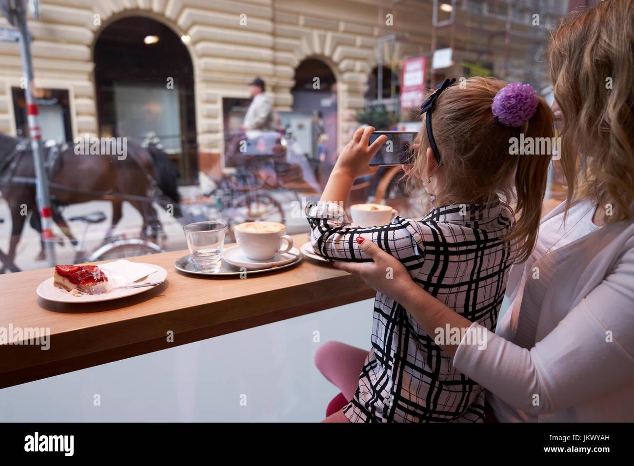 Junge Mutter und Tochter verbringt Zeit im Cafe und Fotos machen Stockbild