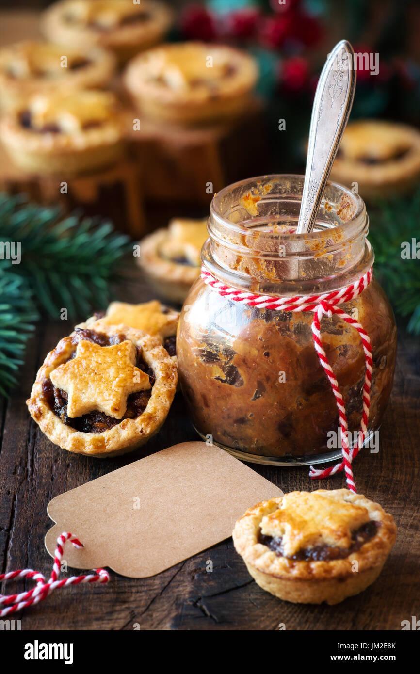 Traditionelle festliche Weihnachten Mince Pies mit ein Glas hausgemachte Hackfleisch und ein leeres tag Stockbild