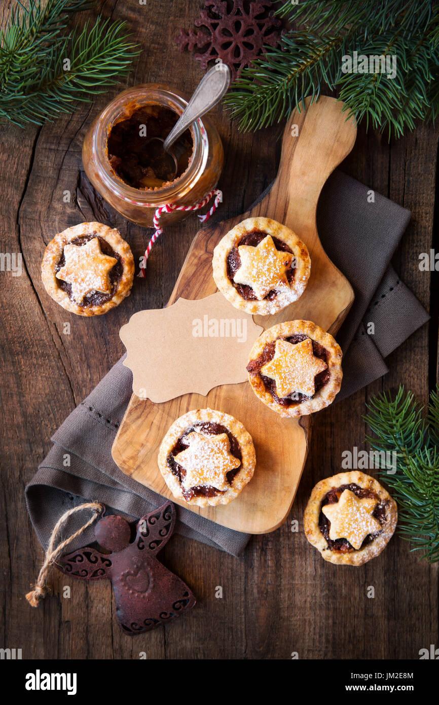 Traditionelle festliche Weihnachten Mince Pies mit ein Glas hausgemachte Hackfleisch und ein leeres Tag. Draufsicht Stockbild