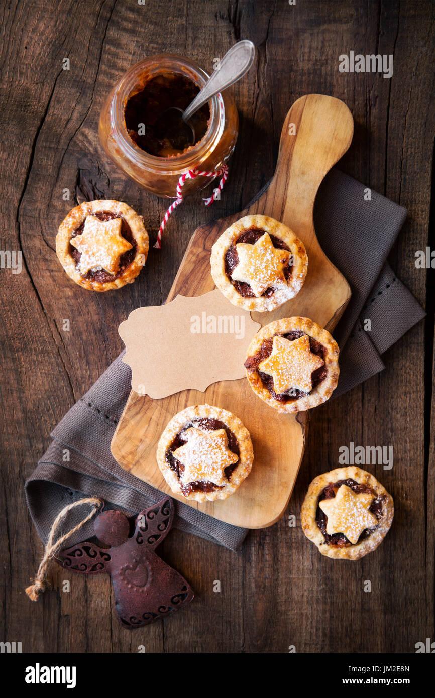 Traditionelle festliche Weihnachten Mince Pies mit ein Glas hausgemachte Hackfleisch und ein leeres Tag. Draufsicht Stockfoto