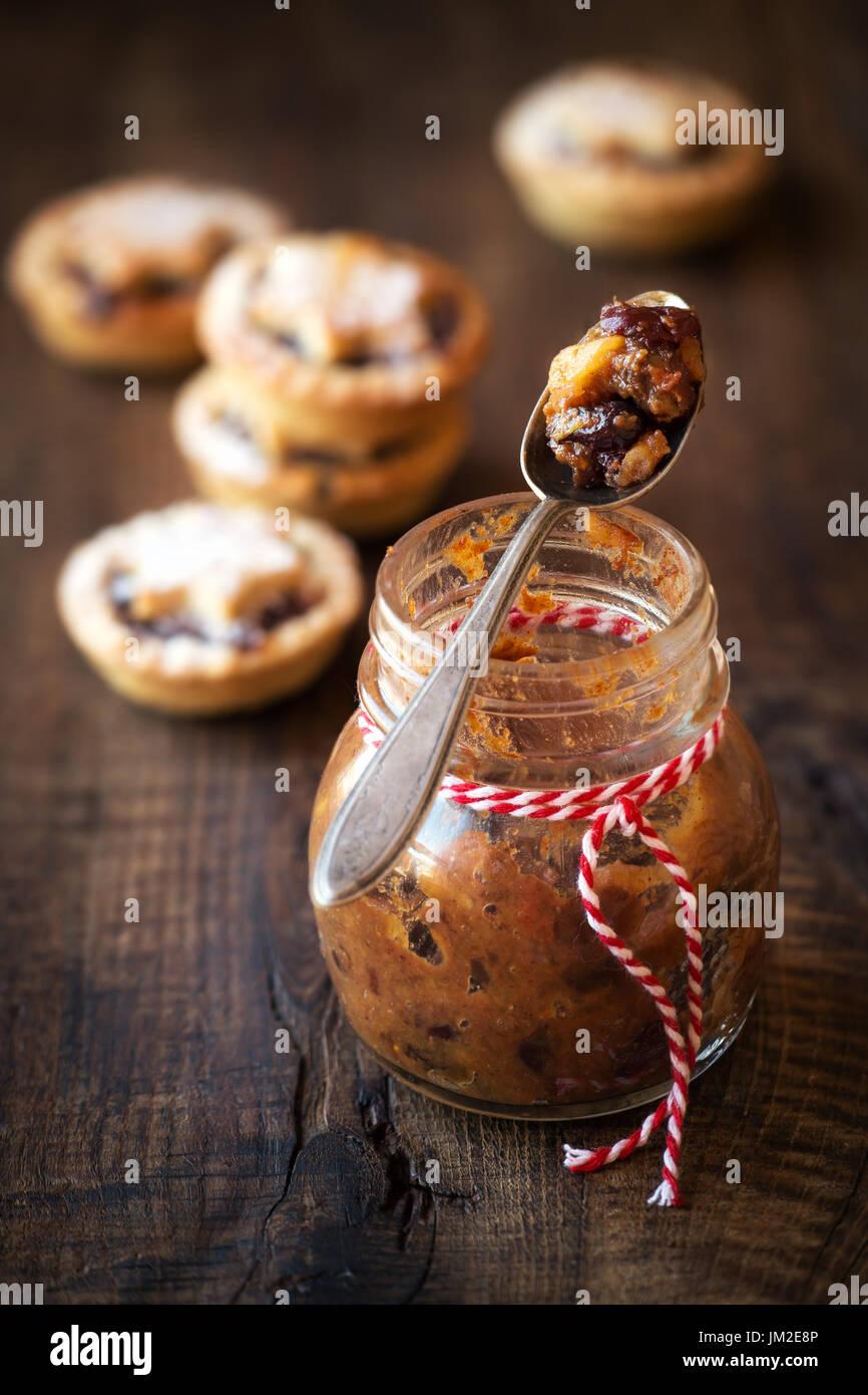 Traditionelle festliche hausgemachte Hackfleisch in ein Glasgefäß und Weihnachten mince Pies im Hintergrund auf rustikalen Holztisch Stockbild