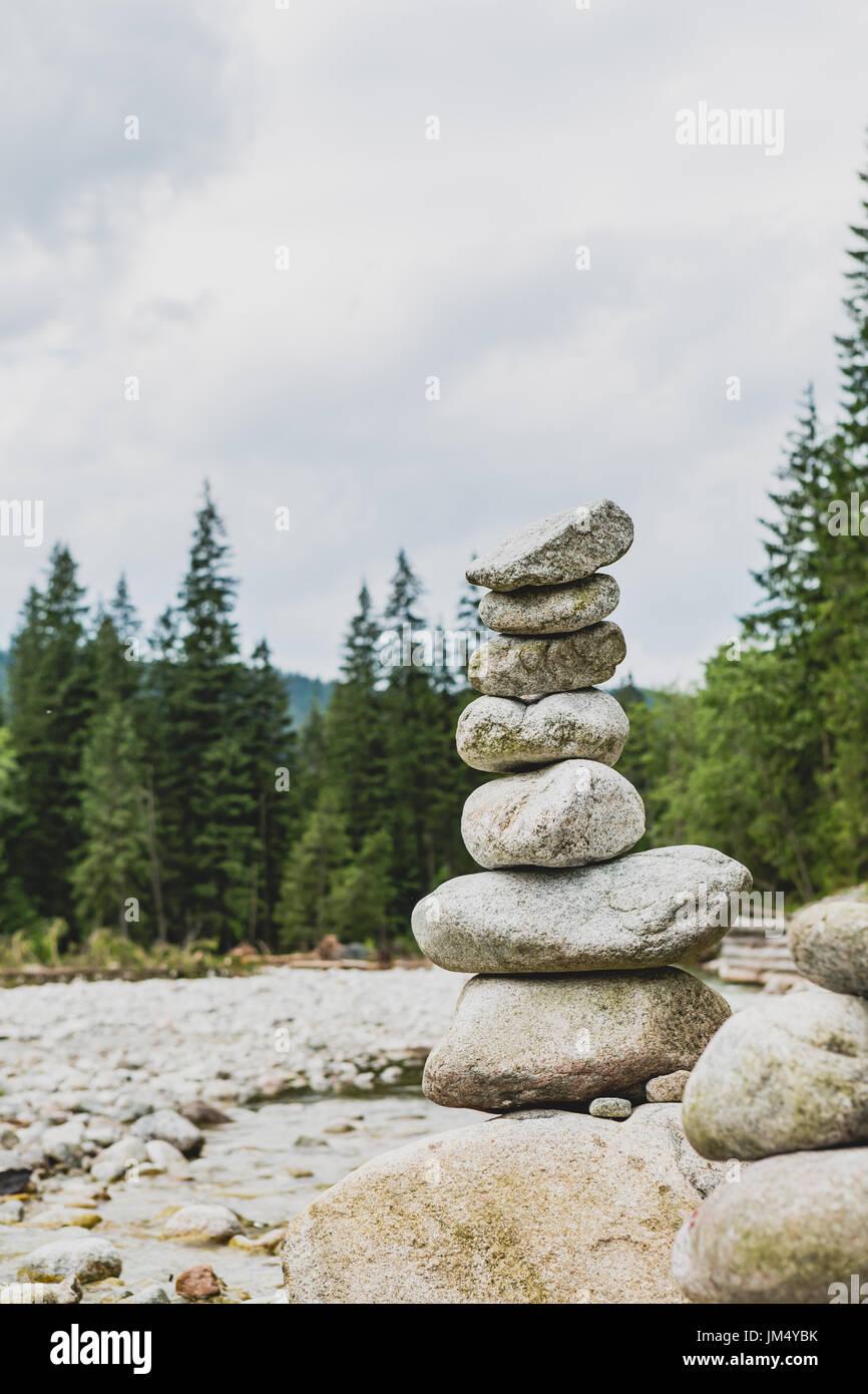 Steinen Gleichgewicht, Hierarchie-Stack über bewölktem Himmel in Bergen. Inspirierende Stabilität Konzept auf Felsen, Fluss und Wald. Stockbild