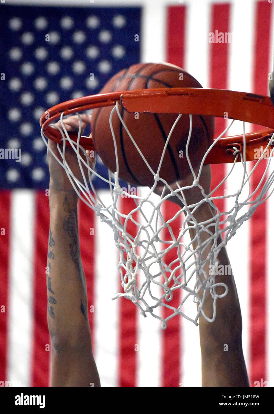 Eine Nahaufnahme eines Basketballs wird getaucht in den Korb mit einer amerikanischen Flagge im Hintergrund Stockbild