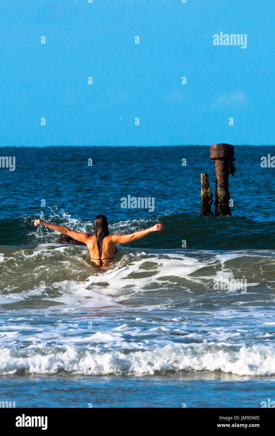 """Mädchen wirft ihre Arme in Heiterkeit als Wellen durch, am """"Wrack"""" Belongil Strand, Byron Bay, New South Wales, Australien. Stockbild"""