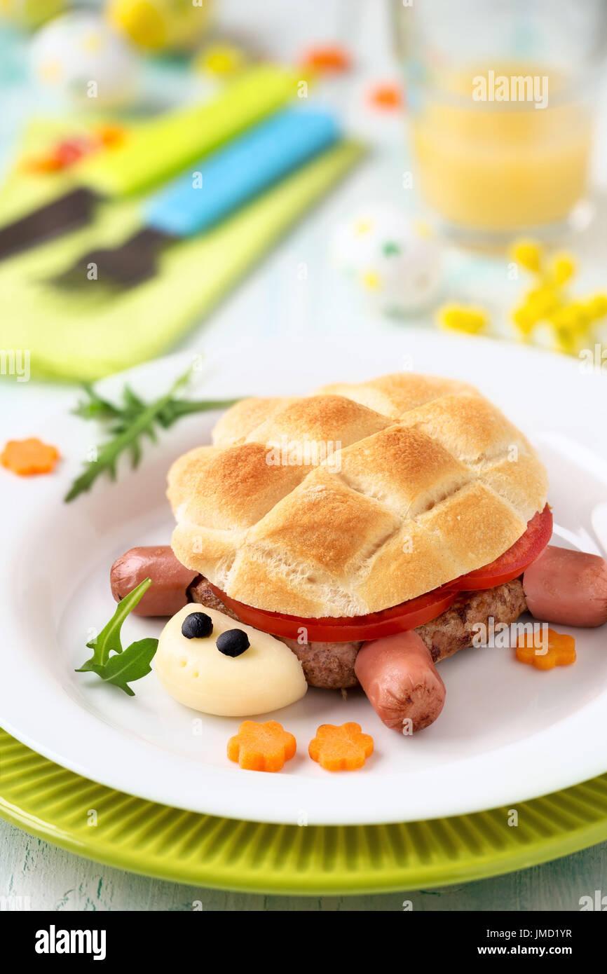 Lustig Essen für Kinder - förmigen niedliche Schildkröte Hamburger gemacht der Boden Fleisch Pattie, Scheiben von frischen Tomaten und Brot mit Ostern Decoraions im Hintergrund Stockbild