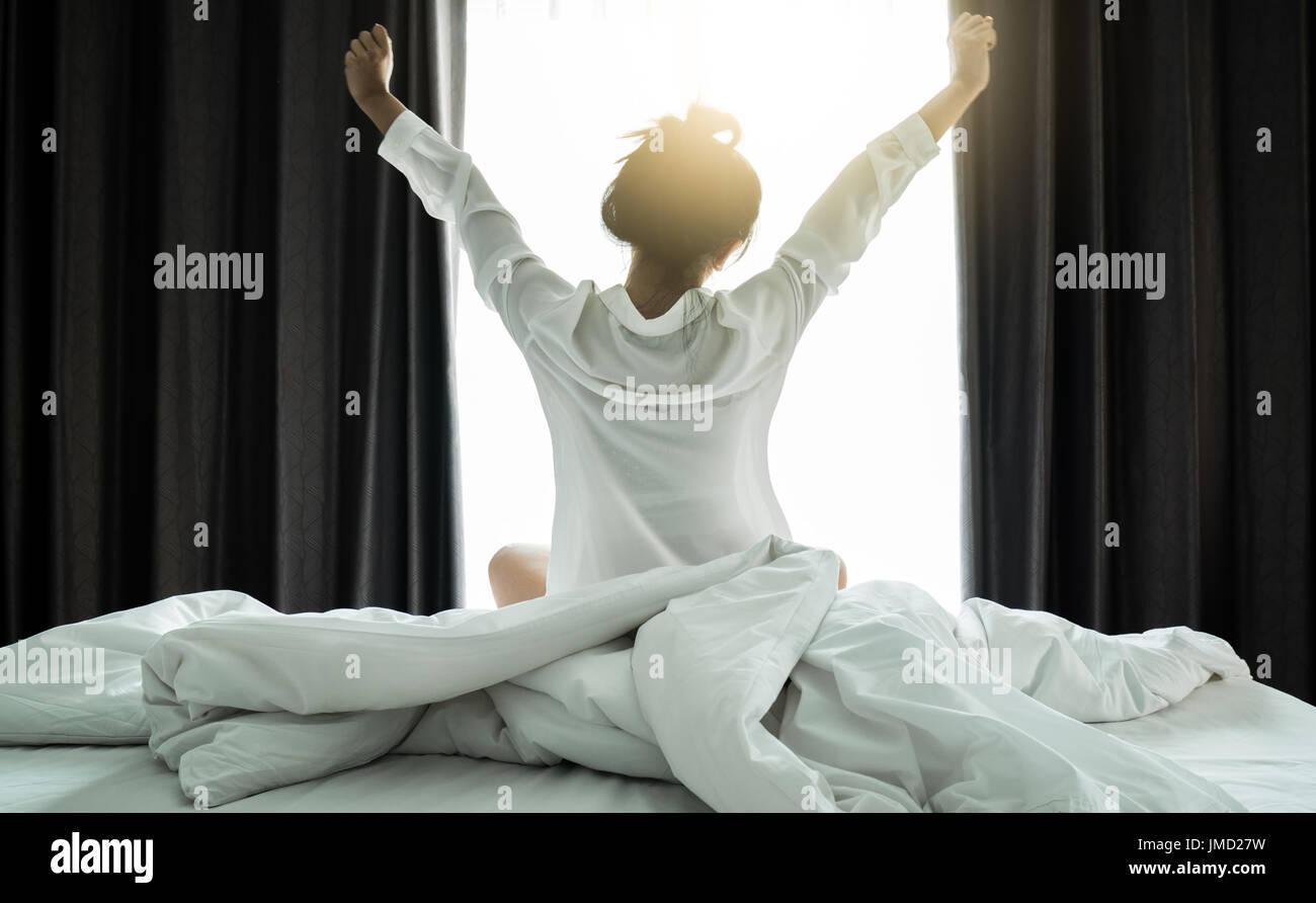 Asiatische Frauen aufwachen aus dem Schlaf. sind dehnen sich in der früh am Wochenende sitzen auf dem Bett im Luxus-Zimmer in Relax und Wochenende-Konzept Stockbild