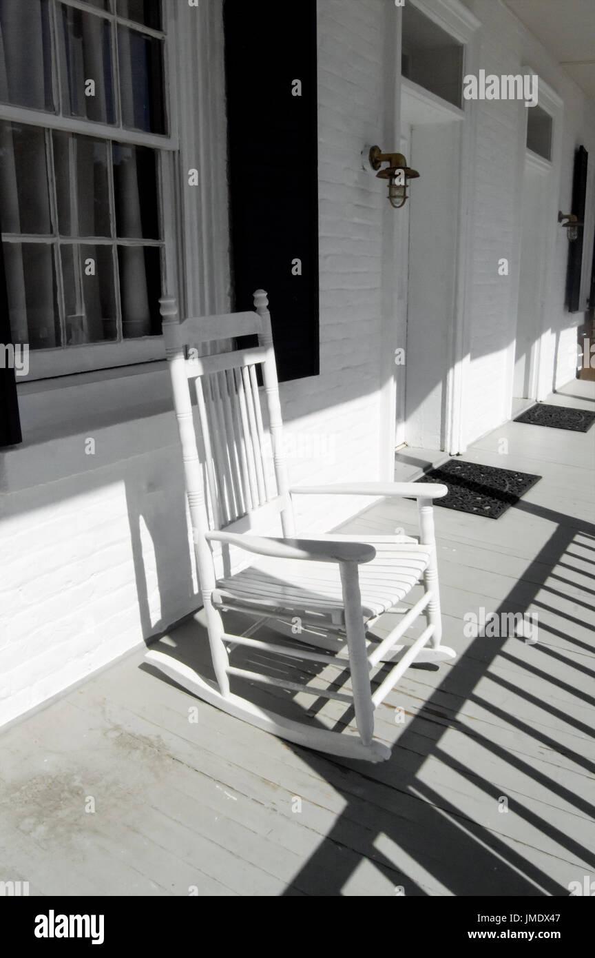 ein weißer schaukelstuhl auf eine alte weiße veranda stockfoto, bild