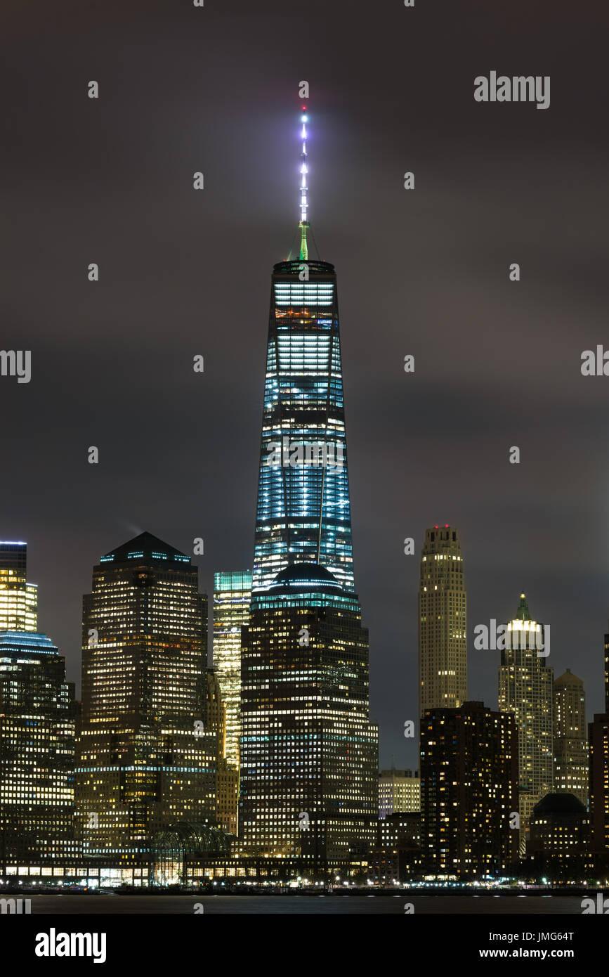 One World Trade Center Zentrum beleuchtet bei Nacht mit Gebäuden unter New York Stockbild
