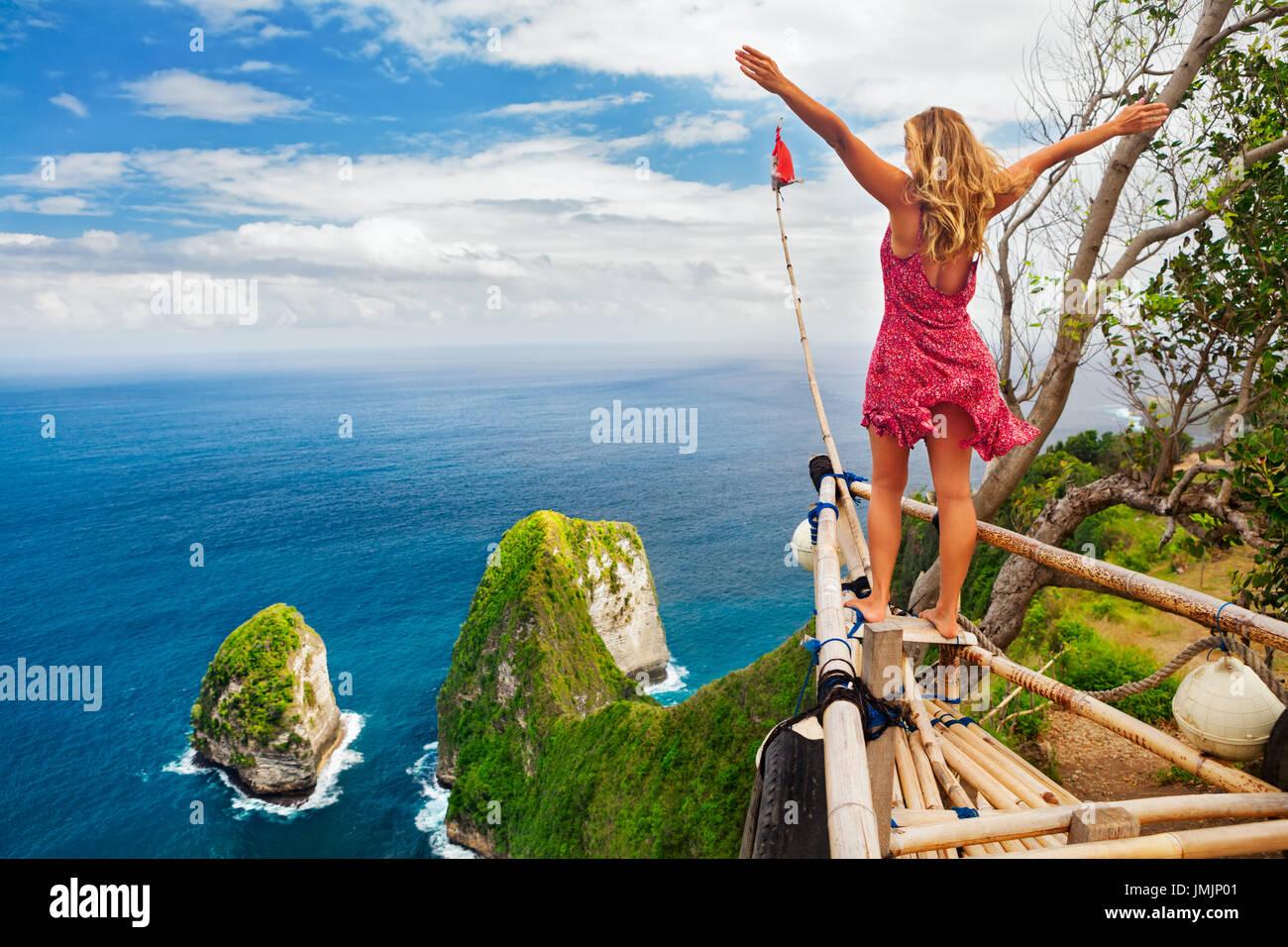 Urlaub mit der Familie Lebensstil. Frau mit hob in Luft Hand Stand am Aussichtspunkt Blick auf schönen Strand unter Klippen. Reiseziel in Nusa Penida Stockbild