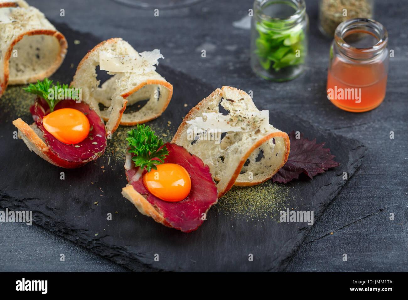 Geheilt von Rindfleisch auf knusprigem Brot mit Eigelb und Parmedgano Käse Stockbild