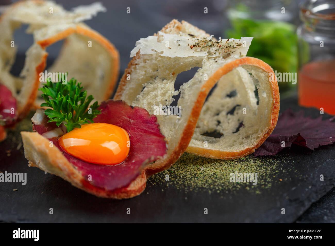 Geheilt von Fleisch auf knuspriges Brot mit Eigelb und Parmegano Käse, Nahaufnahme, selektiven Fokus Stockbild