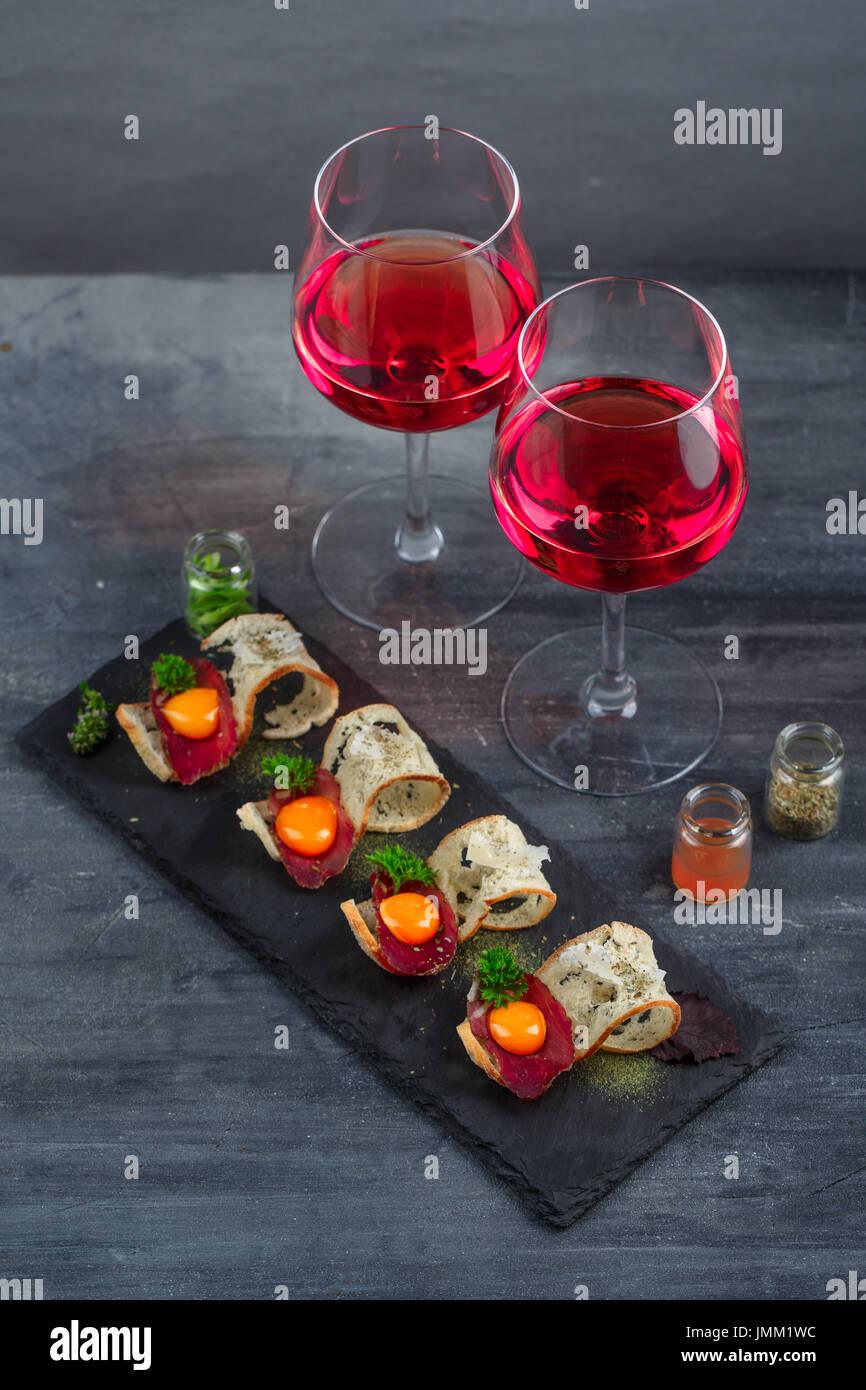 Vorspeisen - Wurst, knuspriges Brot, Eigelb und Käse - auf Steinplatte mit zwei Gläser Wein Stockbild