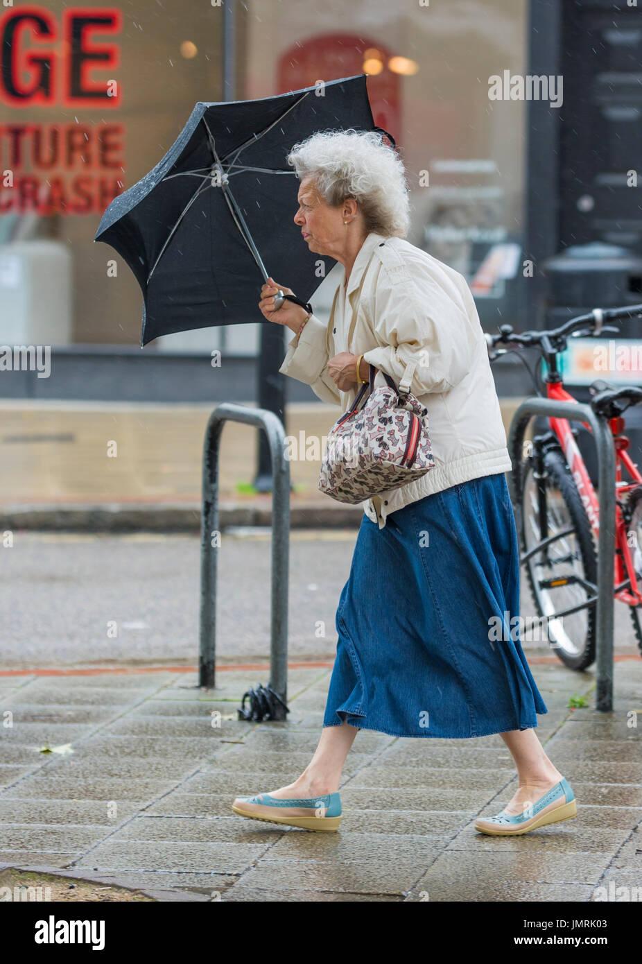 Ältere Dame Frau im Regen und Wind halten ein Regenschirm. Stockbild