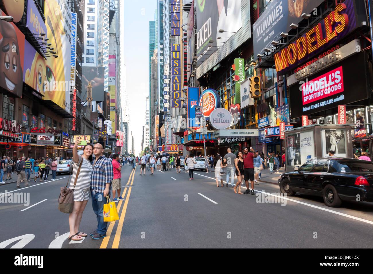 Paare unter Selfies von selbst auf den geschlossenen West 42 Street zwischen Broadway Theater District und 8th Ave., New York City Verkehr. Stockbild