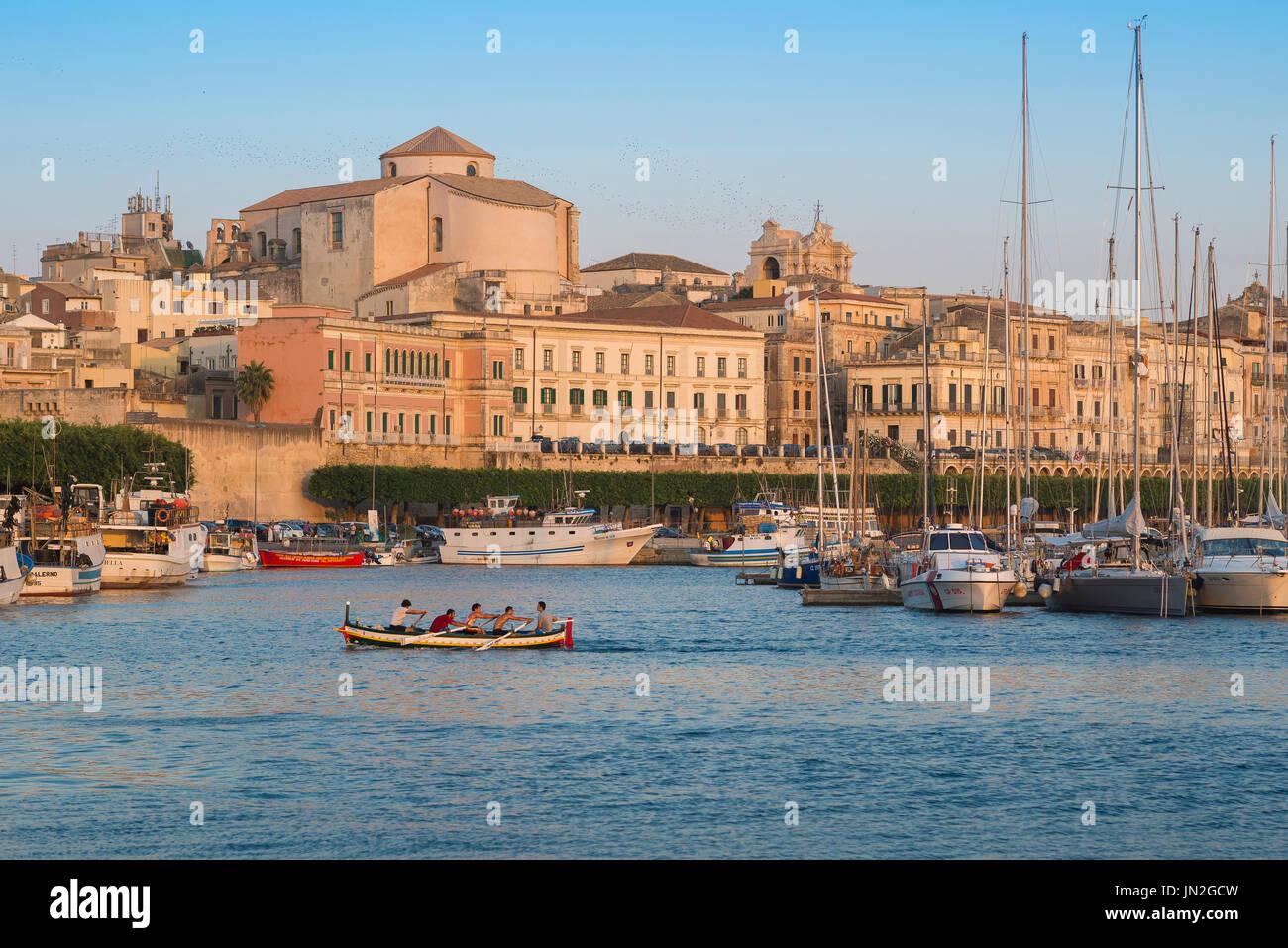 Syrakus Sizilien Stadtbild, Rudern crew Praxis in den Hafen (Porto Grande) der Insel Ortygia (Ortigia), Syrakus, Sizilien. Stockbild
