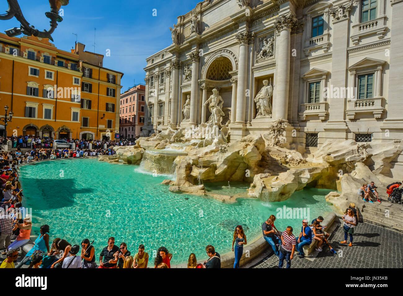 Das Meisterwerk Trevi Founatin an einem warmen Sommertag als Touristen sitzen und Spaß haben Stockfoto