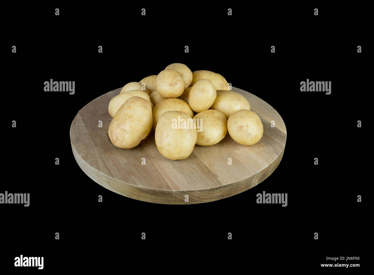 Eine Pyramide aus Ayrshire Frühkartoffeln direkt aus der Beitragszahler Garten und gereinigt und gestapelt auf einem Holzbrett, die dann auf einem schwarzen isoliert ist Stockbild