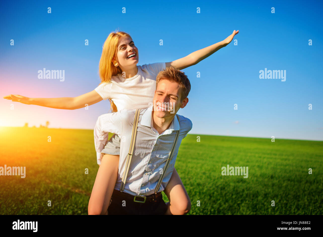 Lächelnd Mann hält auf seinem zurück glücklich Frau, zieht seine Arme und simuliert einen Flug vor dem Hintergrund des blauen Himmels und das Grün fie Stockbild