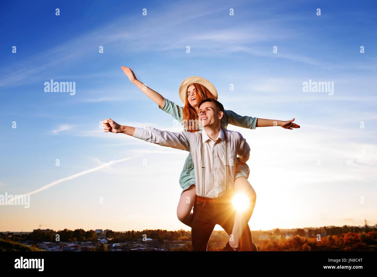 Junger Kerl Huckepack fröhlich Freundin wie Flugzeug auf dem Hintergrund des Himmels. Stockbild