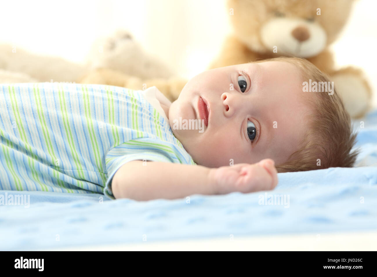 Porträt eines Babys auf einem Bett liegend und mit Blick auf Sie Stockfoto
