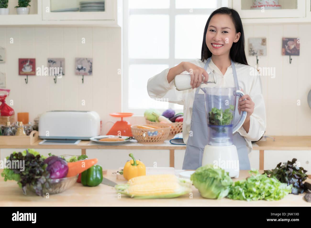Gemüse-Smoothie. Asiatin macht grüne Smoothies mit Blender zu Hause in der Küche. Gesunden roh essen Lifestyle Konzept Porträt von schöne junge Stockbild