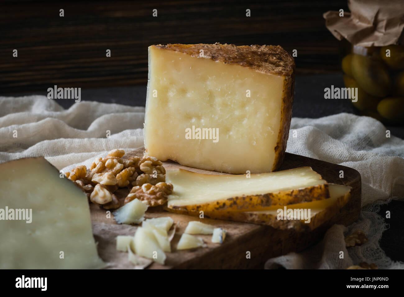 Käseplatte von spanischen Käse Manchego gehackt und in Scheiben geschnitten italienischen Pecorino Toscano) auf Holzbrett mit grünen Oliven im Glas und Nussbaum Stockbild