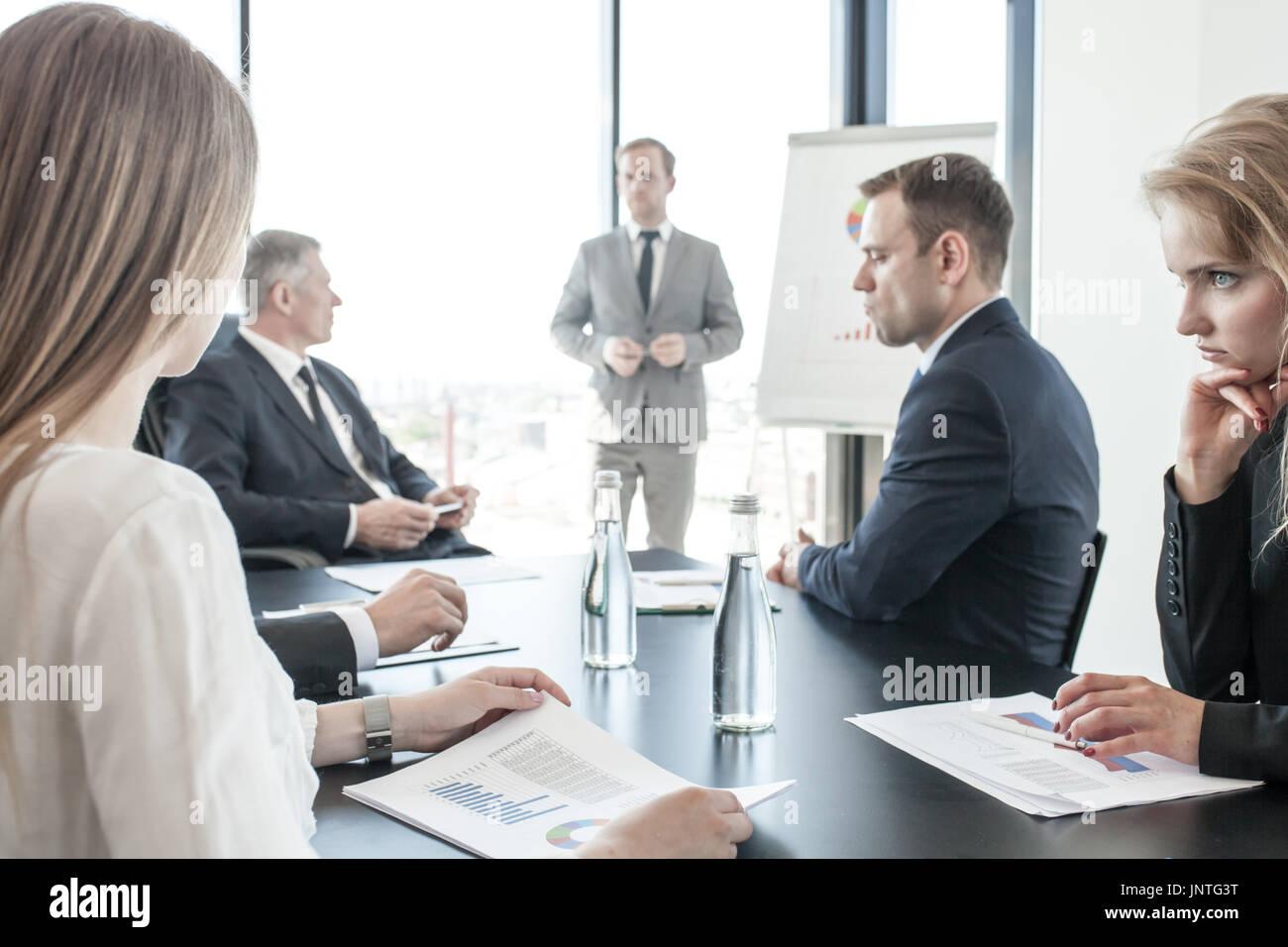 Gruppe von Geschäftsleuten in Sitzung beobachten Präsentation von Berichten in Diagrammen und Grafiken auf Flip-Chart in offfice Stockbild