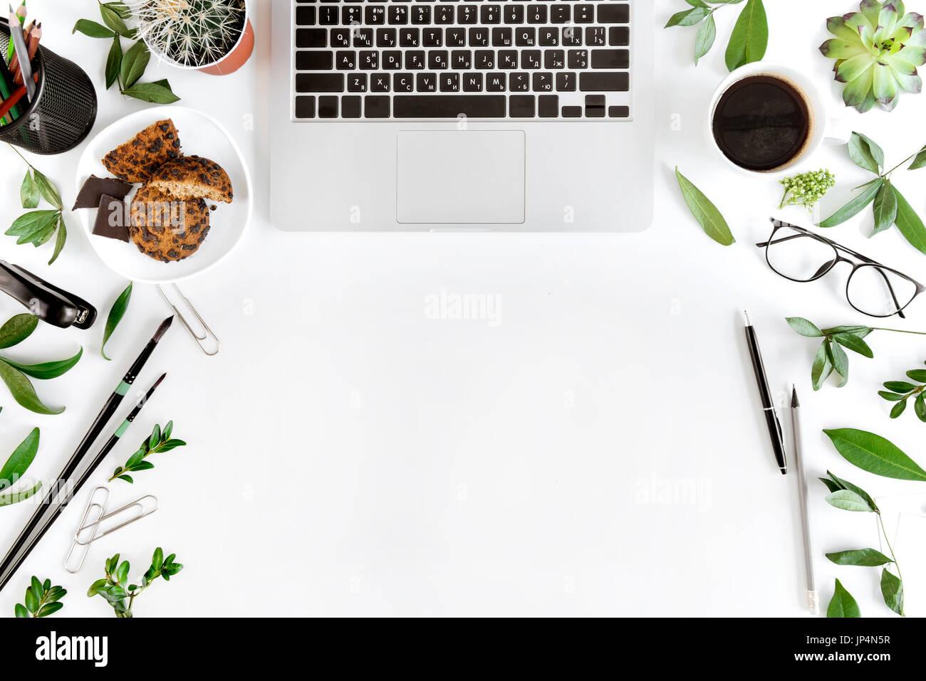 Draufsicht des Laptops, Büromaterial und Kaffee am Arbeitsplatz isoliert auf weiß, drahtlose Kommunikations-Konzept Stockbild