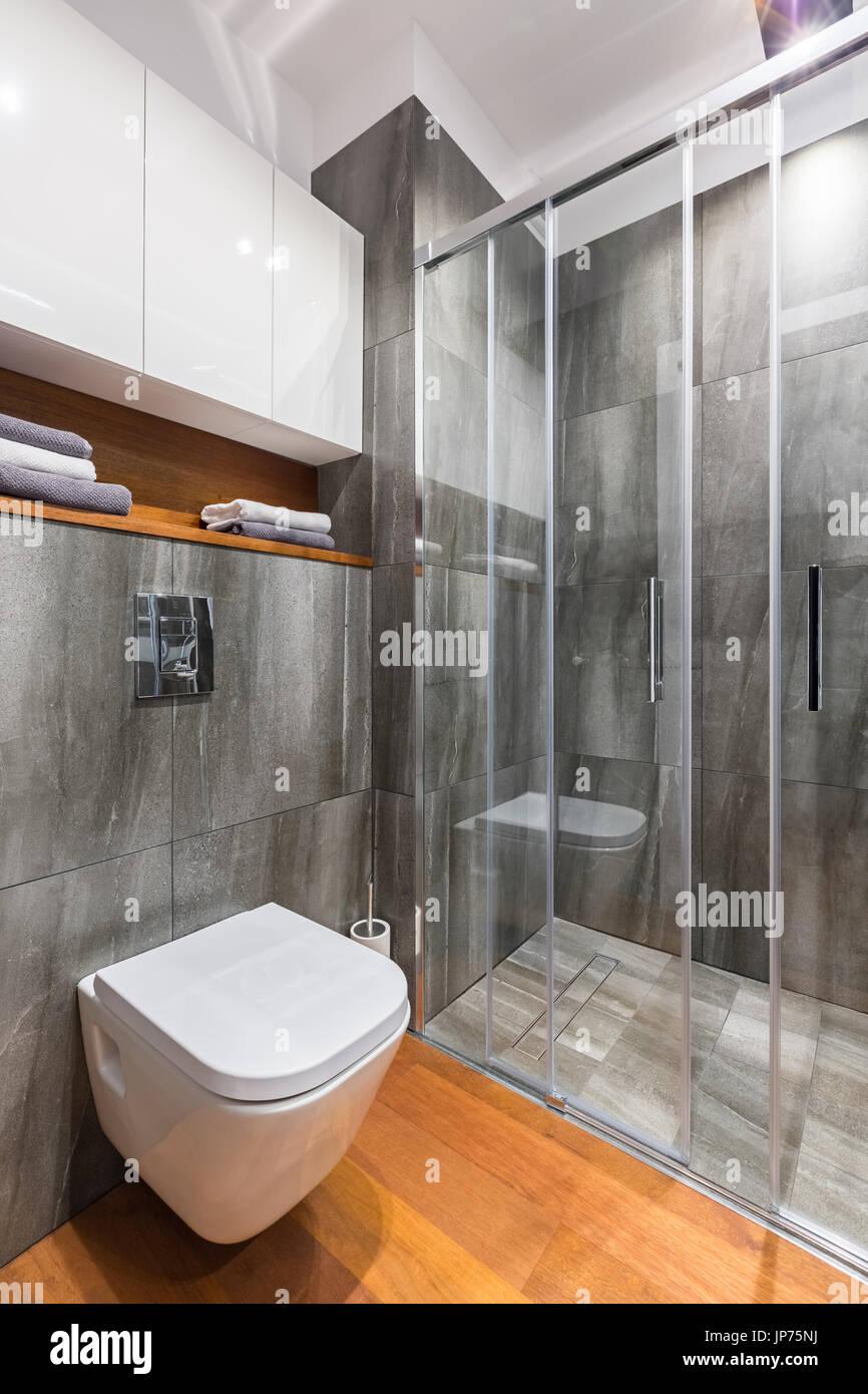 Graue Badezimmer mit begehbarer Dusche und weiße Toilette ...