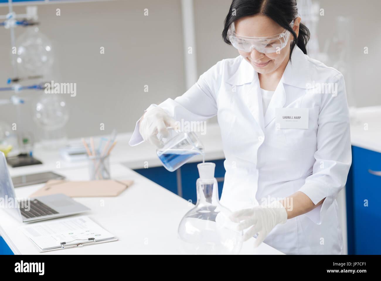 Fröhliche professionelle Wissenschaftler arbeiten mit Reagenzien Stockbild