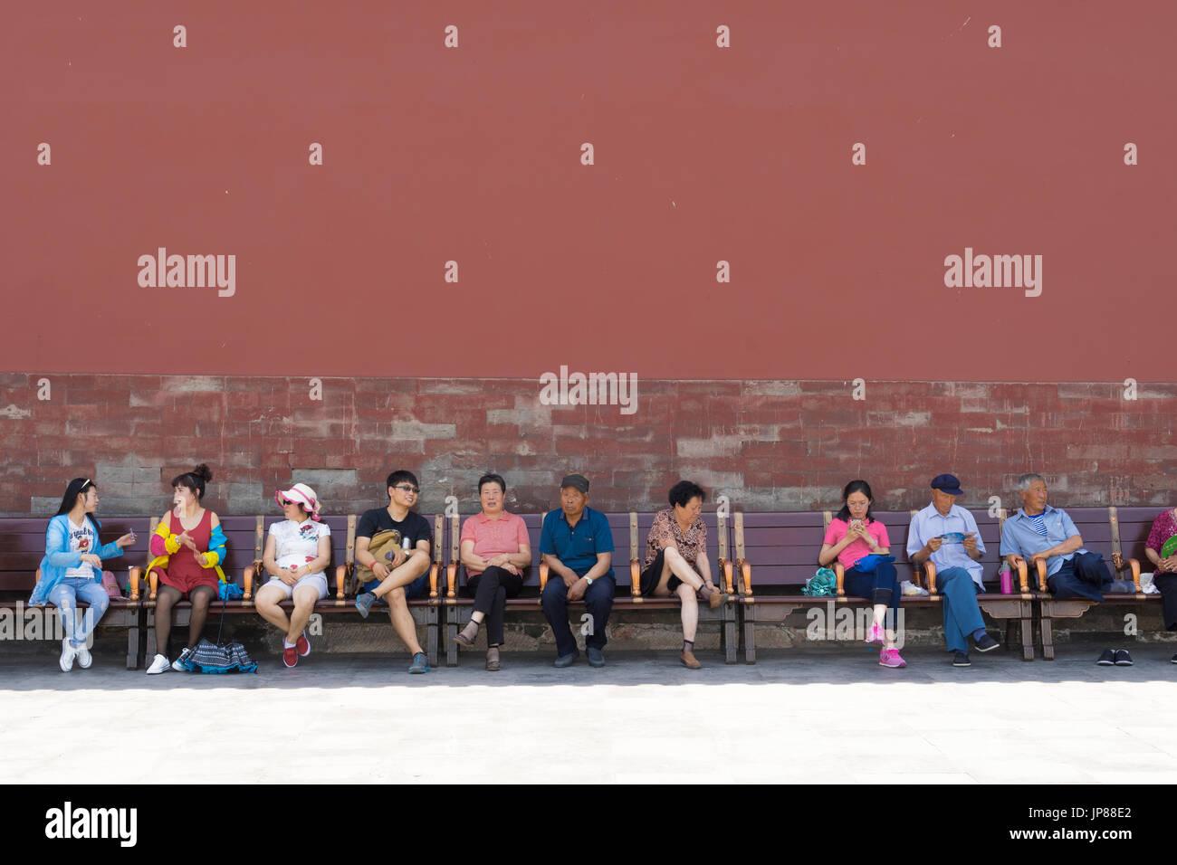 Chinesische Touristen aller Altersgruppen sitzen auf Bank am verbotenen Stadt in Peking - einige ruhen, einige sprechen, eine auf ihr Handy Stockbild