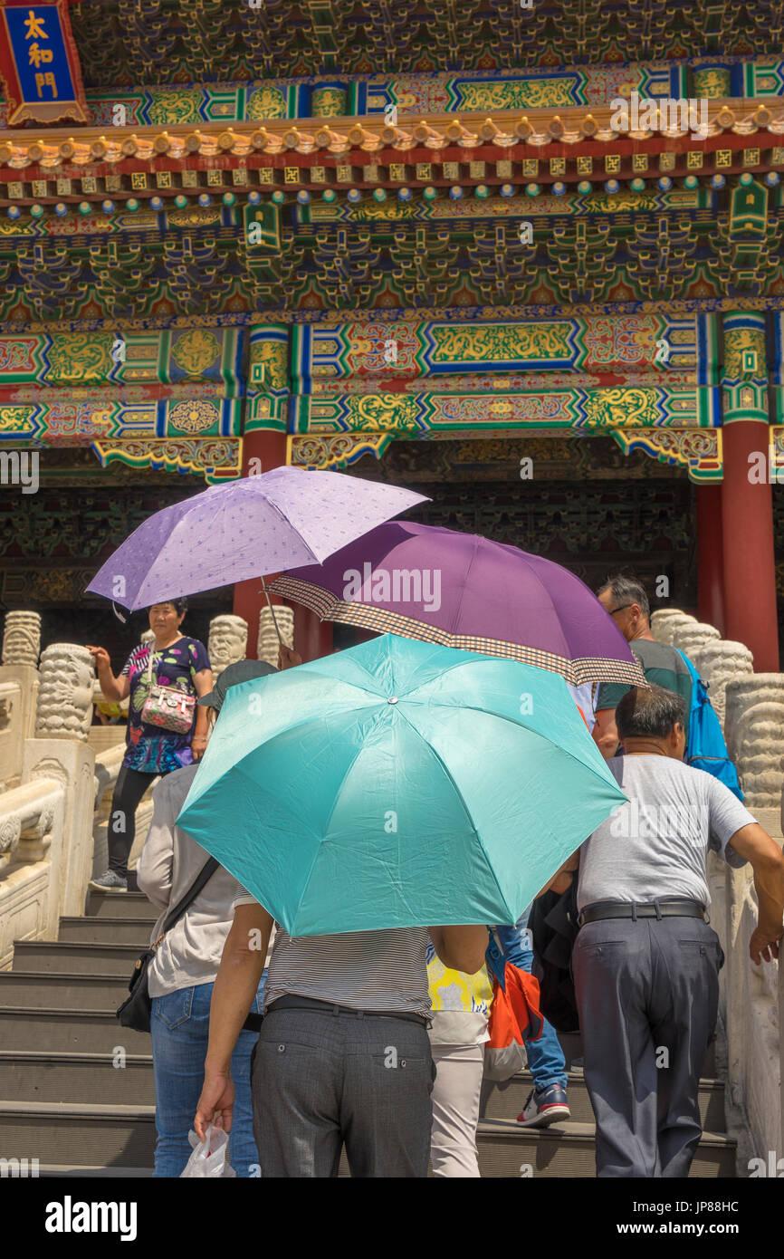 Touristen halten bunte Schatten Sonnenschirme nähert sich die Halle der höchsten Harmonie in der verbotenen Stadt, Peking, China Stockbild