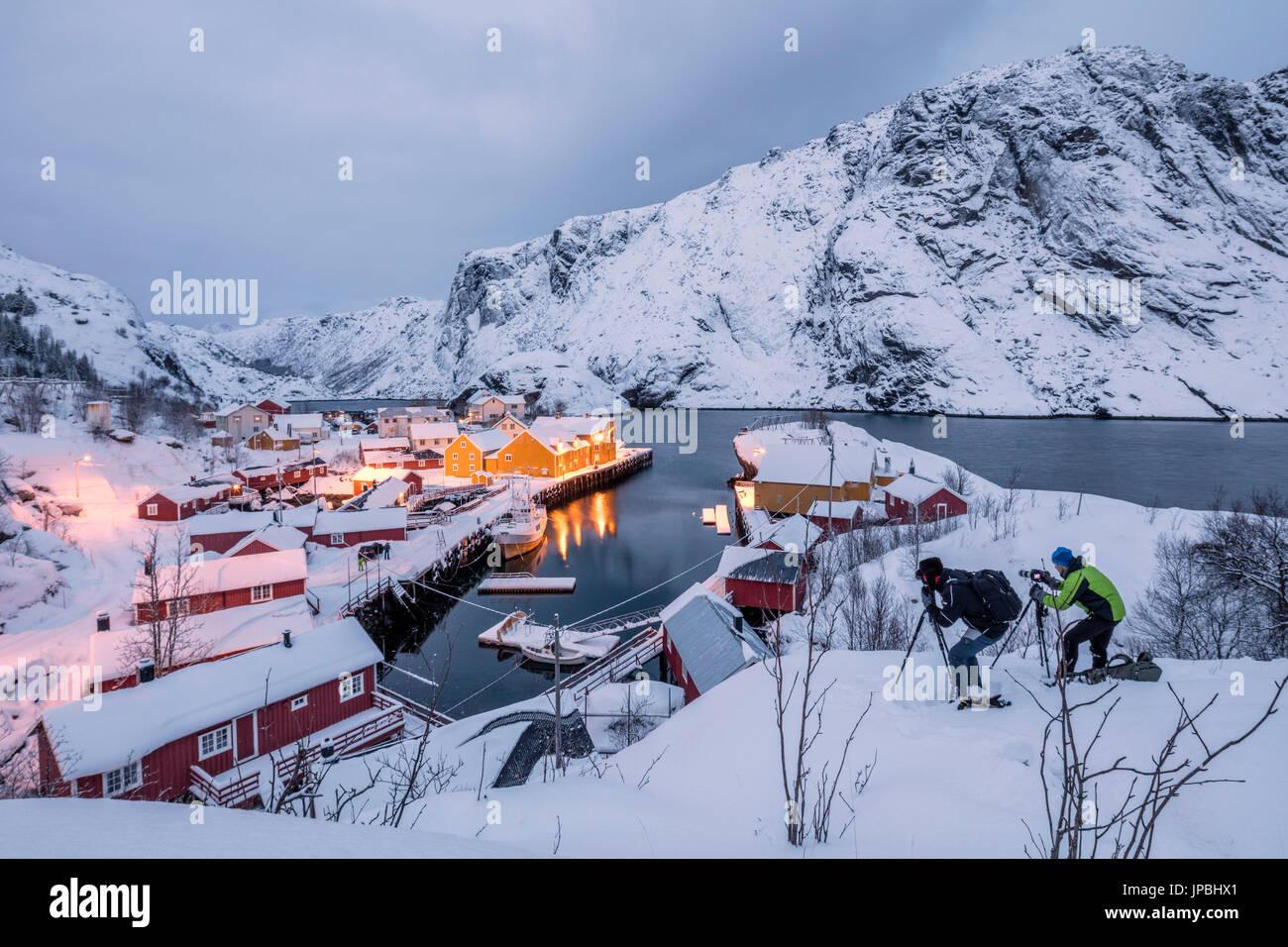 Fotografen in der Abenddämmerung in der Nähe des Fischerdorfes beschneit Nusfjord Nordland Lofoten Inseln Norwegen Nordeuropa Stockbild