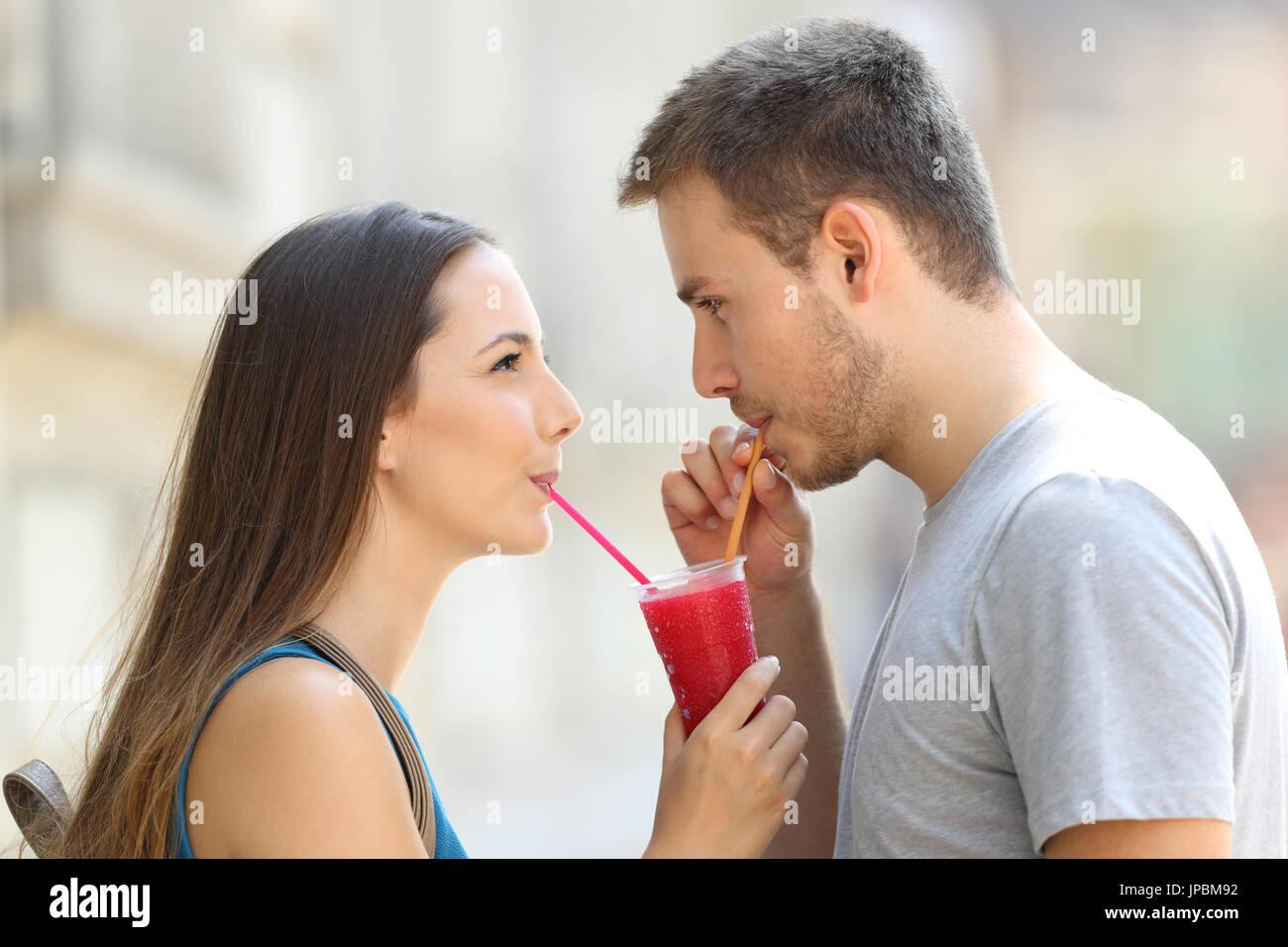 Seite Ansicht Porträt ein glückliches Paar, schlürfen einen Matsch zusammen draußen auf der Straße Stockfoto
