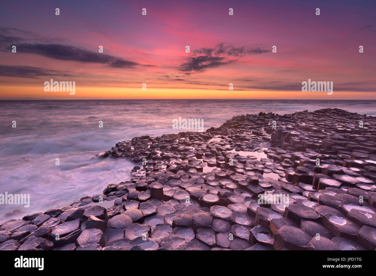 Sonnenuntergang über den Basalt Felsformationen des Giant's Causeway auf der Küste Nordirlands. Stockbild