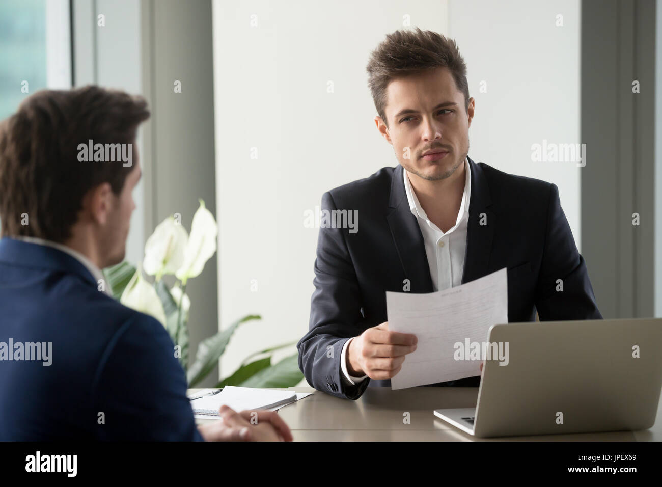 Misstrauisch Geschäftsmann hält Dokument lesen schlecht Lebenslauf an Stockbild