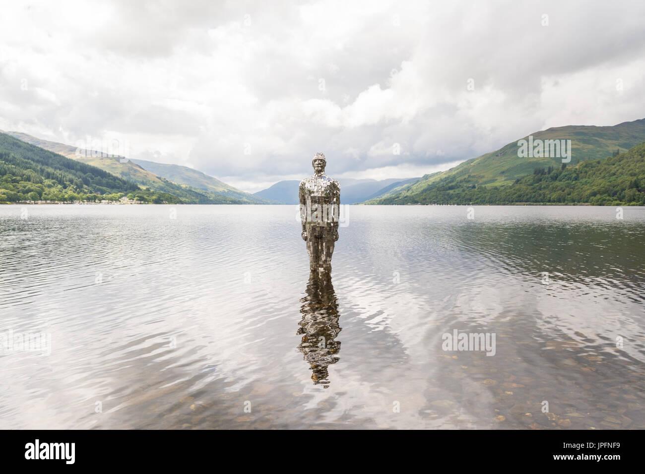 """Loch Earn, St. Fillans, Perth and Kinross, Schottland, UK. 1. August 2017. UK-Wetter - eine sich abzeichnende Figur mit dem Titel """"Still"""", aber lokal bekannt als Spiegel Mann ertragen täglich kräftige Schauer mit kurzen Teils sonnig. Das Kunstwerk des Künstlers Rob Mullholland besteht aus gespiegelten Fliesen. Bildnachweis: Kay Roxby/Alamy Live-Nachrichten Stockbild"""