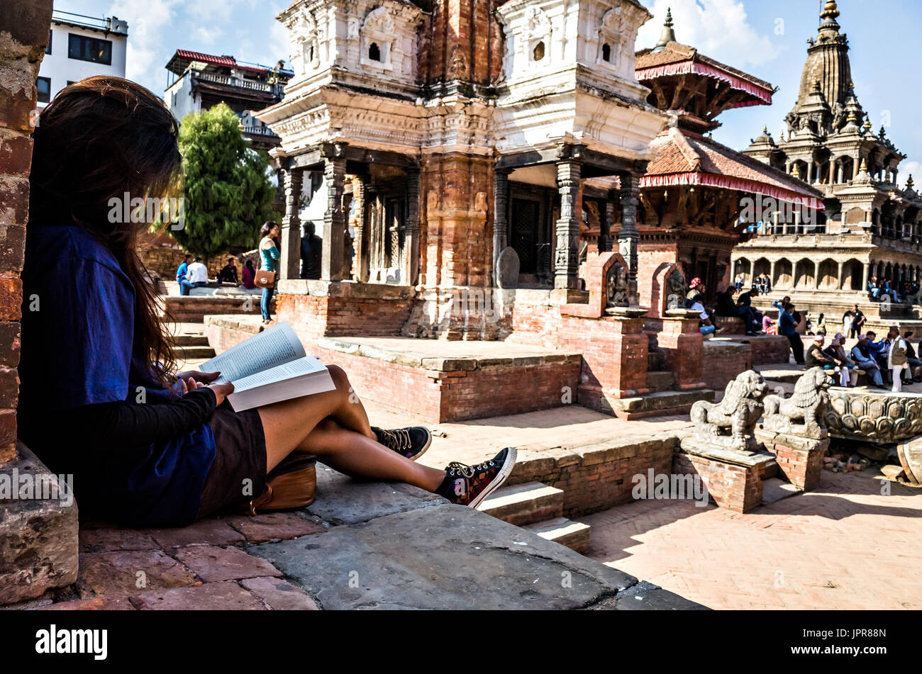 Straße Foto eines Mädchens, ein Buch lesen, Patan Durbar Square, Lalitpur, Nepal Stockbild