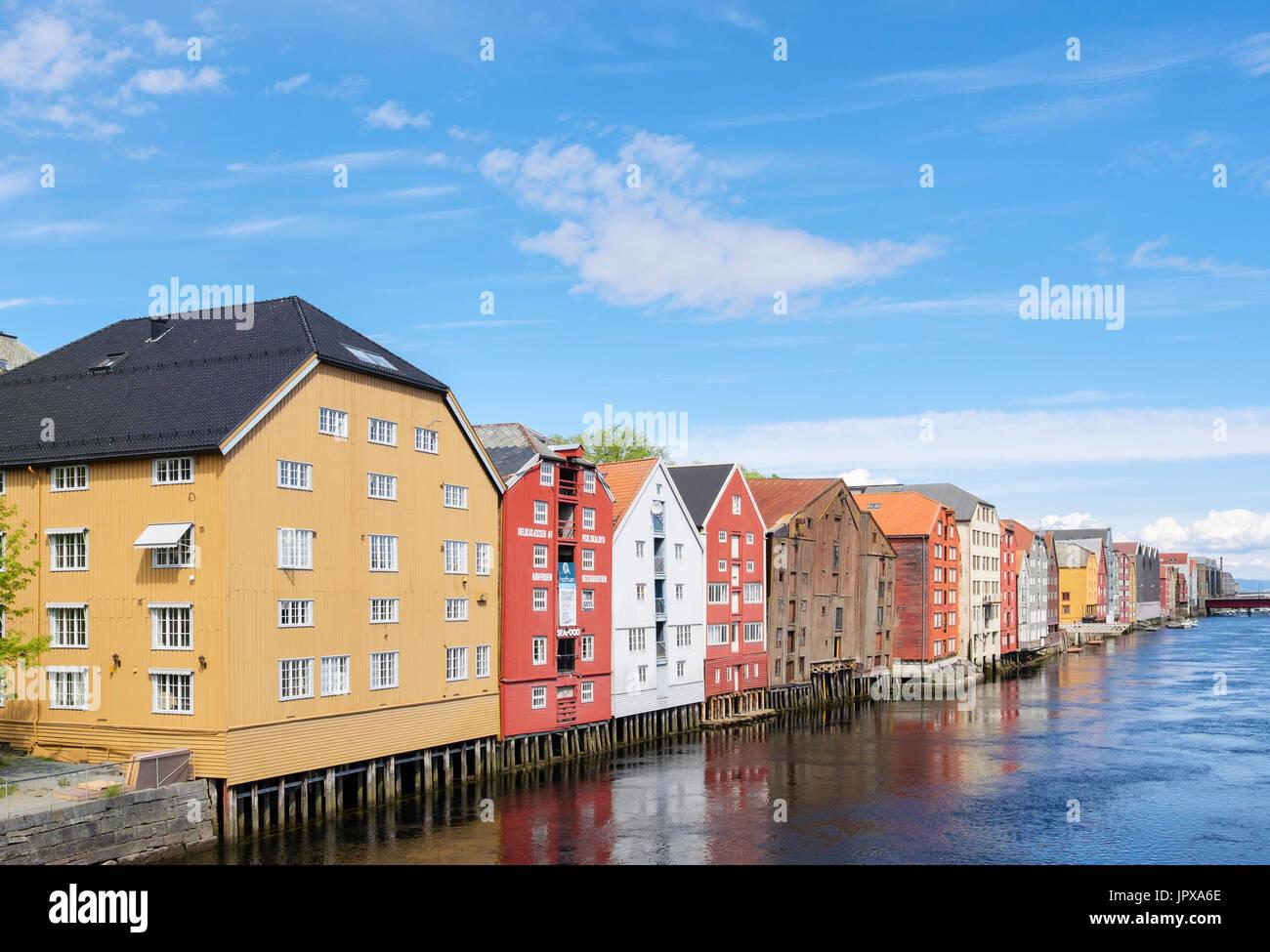 Bunte historische hölzerne Lagergebäude auf Stelzen am Fluss Nidelva Wasser in der alten Stadt im Sommer. Trondheim Norwegen Skandinavien Stockbild