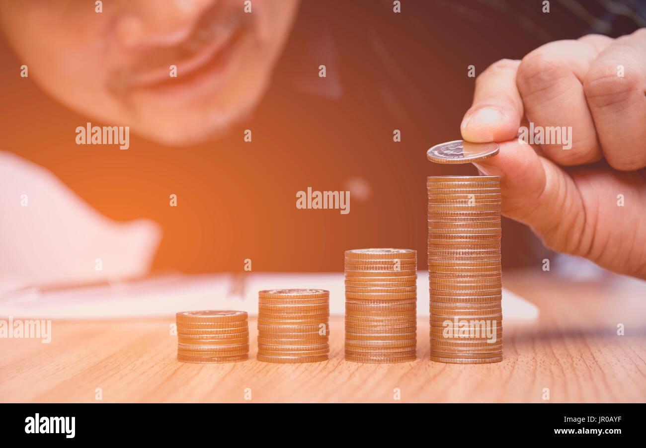 Spart Geld-Konzept und Hand setzen Geld Münze-Stack für Unternehmen wächst Stockbild