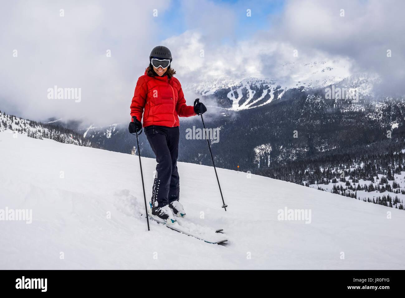Eine weibliche Skifahrer posiert für die Kamera auf einem Ski Hill zu einem Skigebiet, Whistler, British Columbia, Kanada Stockbild