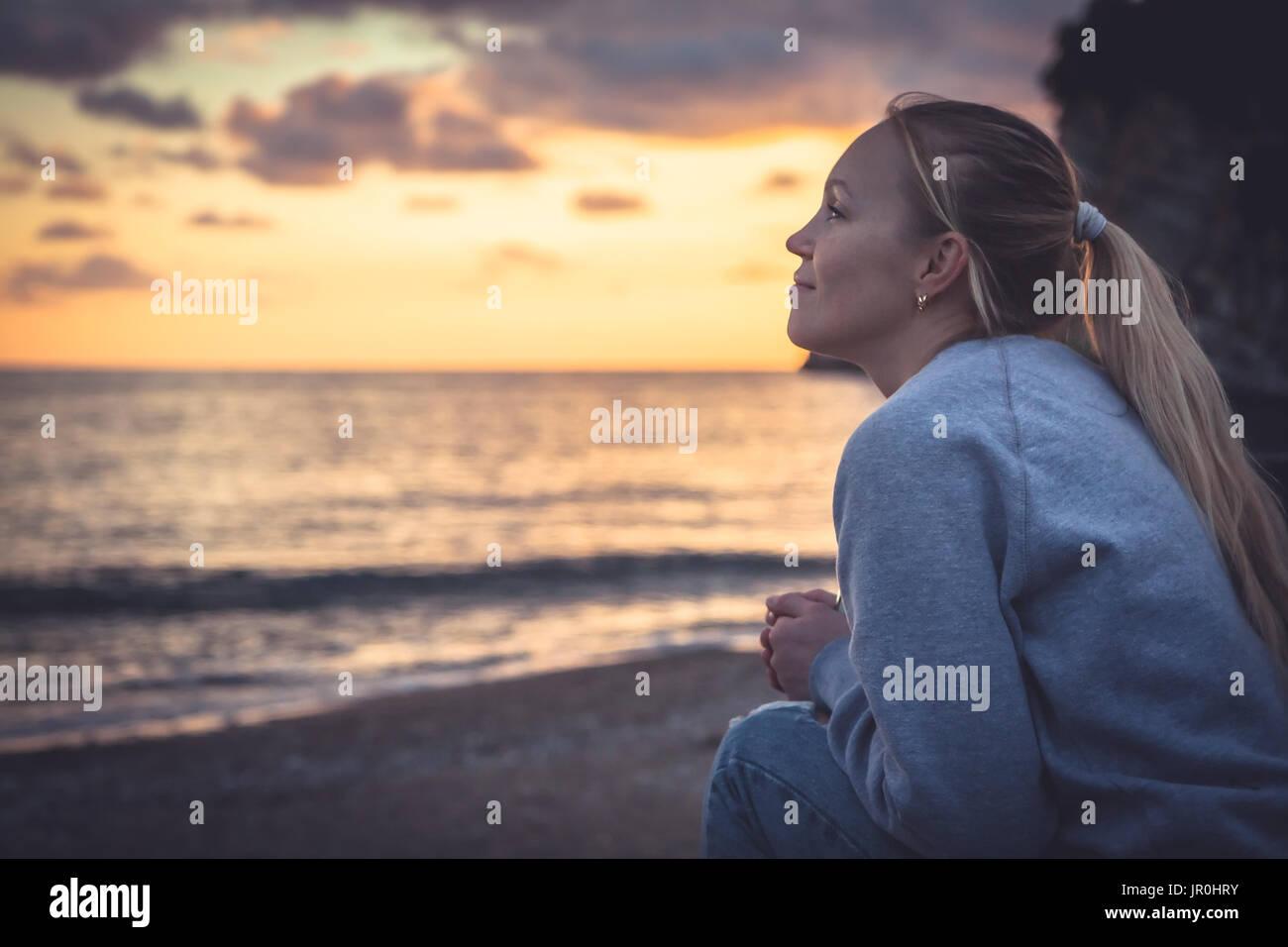 Nachdenkliche einsame lächelnde Frau mit Hoffnung in Horizont bei Sonnenuntergang am Strand Stockbild