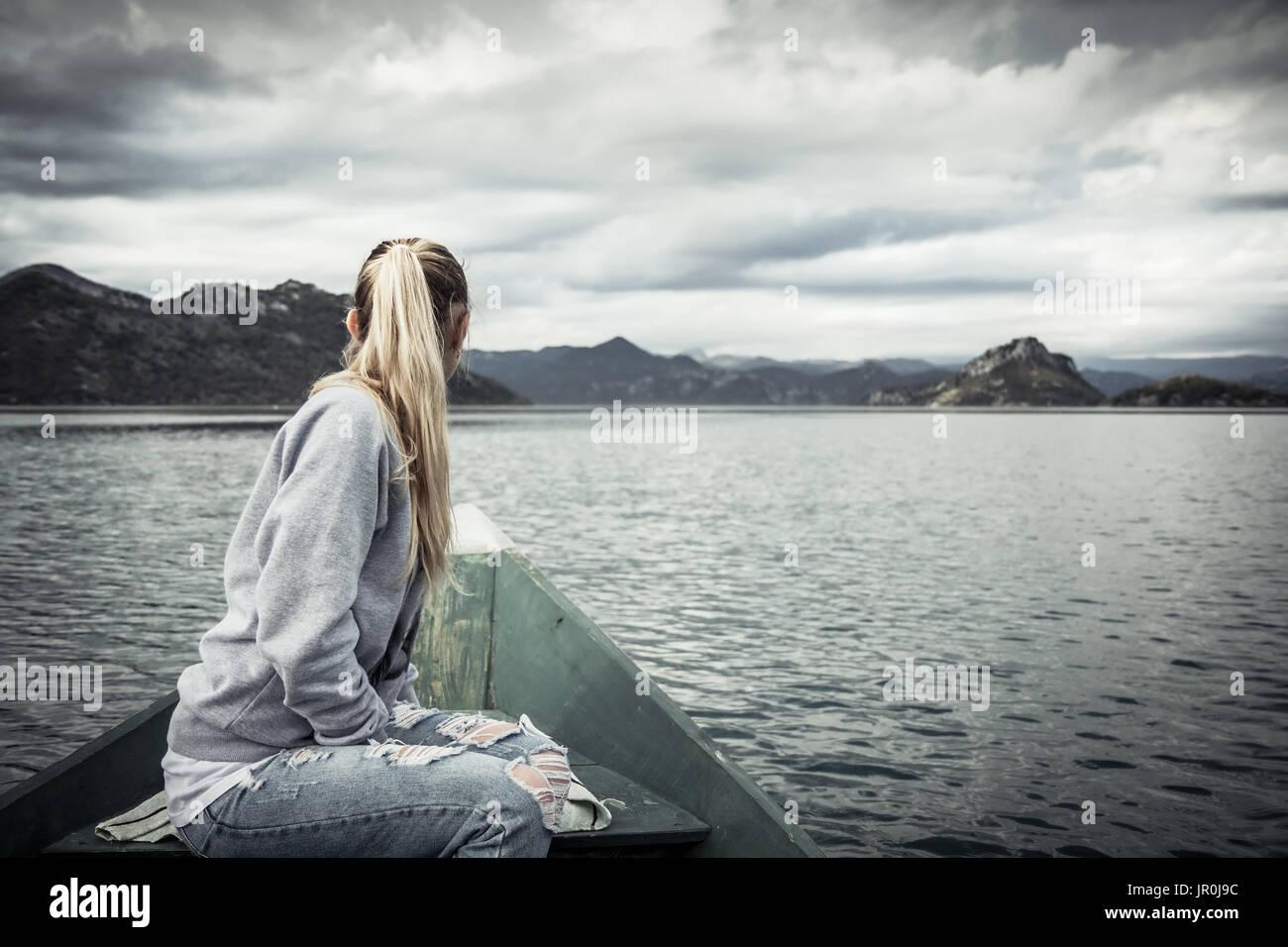 Nachdenkliche junge Frau Touristen in schöner Landschaft, am Bug des Bootes auf dem Wasser schwimmend in Richtung Ufer im bewölkten Tag mit dramatischen Himmel Stockbild