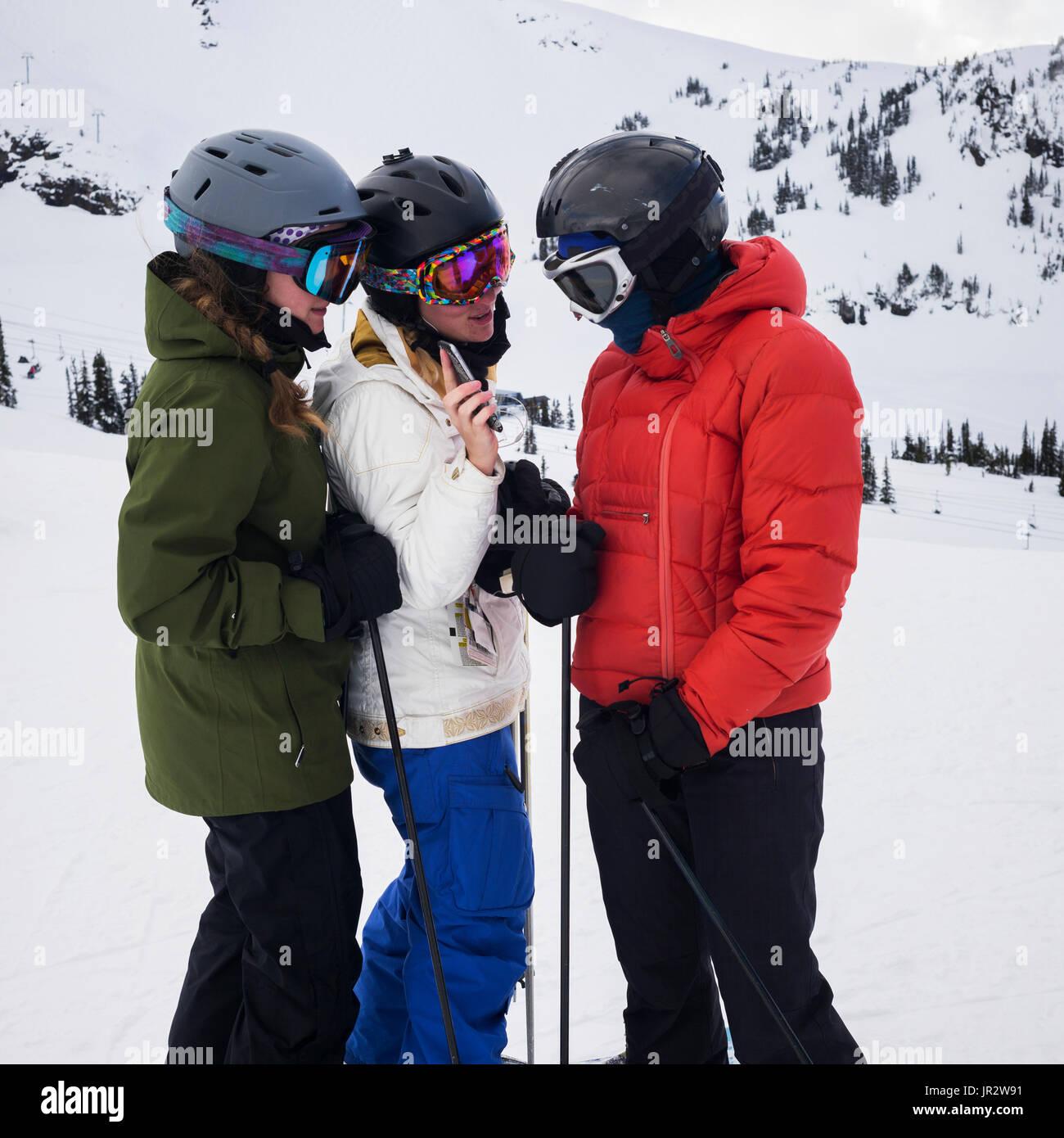 Drei junge Erwachsene Frauen auf der Suche nach ein Handy beim Stehen und Bereit zum Ski an einem Skigebiet, Whistler, British Columbia, Kanada Stockbild