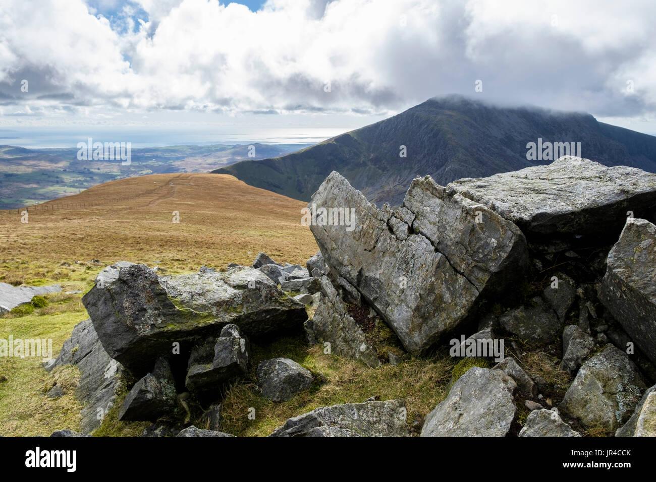 Gebrochenen Felsbrocken auf Mynydd Tal-y-Mignedd mit Craig Cwm Silyn darüber hinaus auf Nantlle Ridge in Berge von Snowdonia-Nationalpark. Gwynedd Wales UK Stockbild